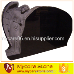 Angel leaning black tombstone