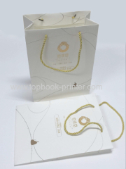 Custom designed gold stamping craft paper packaging bag with white cotton rope