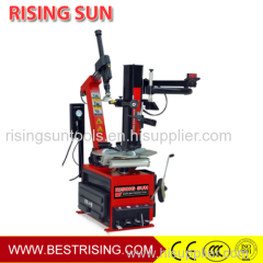 Tilt back tyre fitting machine with helper arm